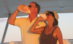 Captain Tom and Alicia blow queen conch shells at sundown in the Caribbean aboard Tom's boat.